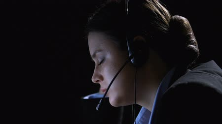 телемаркетинг : Female call center agent taking off headphones, exhausted on night shift closeup Стоковые видеозаписи