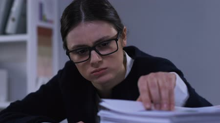 отчаянный : Stressed woman looking through stacks of documents, overloaded with paperwork Стоковые видеозаписи