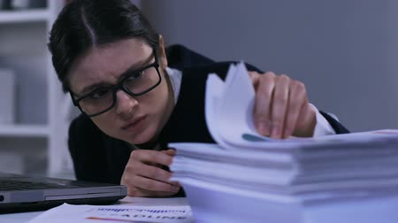 desperate : Unmotivated stressed office worker looking through papers, work overload closeup
