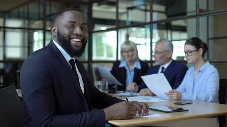 trabalho em equipe : Happy afro-american businessman smiling camera sitting office table, career Vídeos