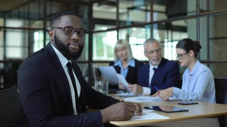 trabalho em equipe : Black male manager in suit and eyeglasses looking camera sitting meeting room