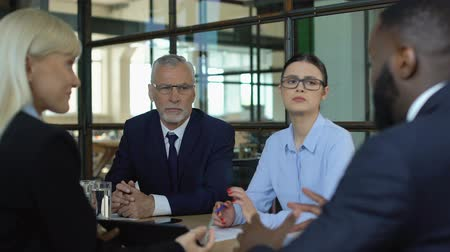 контракт : Aged businessman and woman looking unhappy with deal terms offered by partners