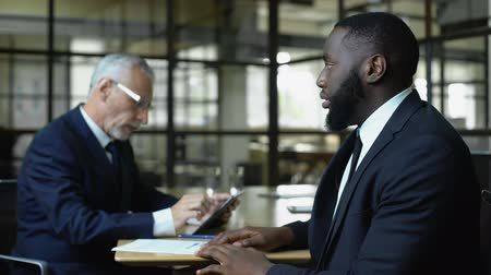 incapacidade : Mature business man refusing african job candidate reading resume on tablet