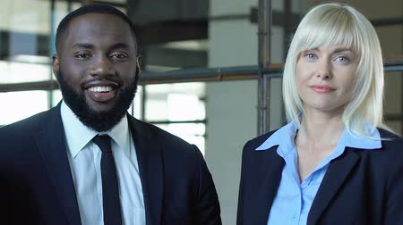 příležitost : Blond businesslady and black man smiling on camera, race gender equality at work