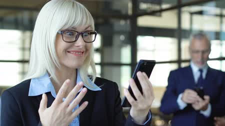 восхищенный : Excited businesswoman showing yes gesture, reading great news on phone, success Стоковые видеозаписи