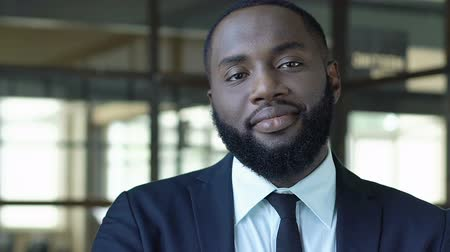 official : Self-confident black businessman looking on camera, high post, successful career