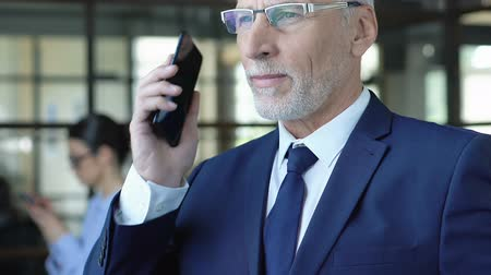 сообщений : Respectable elderly businessman calling partners by phone, making appointment