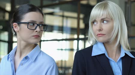 аргумент : Two women looking different sides, competing at work, blond and brunette rivalry Стоковые видеозаписи