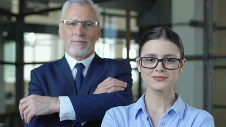 konsultant : Male ceo with female secretary looking on camera, insurance agency advertising