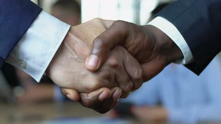 контракт : Afro-american and caucasian businessman shaking hands, international cooperation