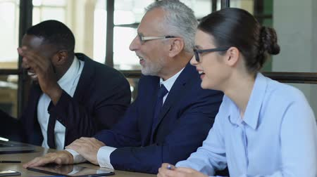workgroup : Employees laughing relaxing at business meeting, friendly atmosphere in office Stock Footage