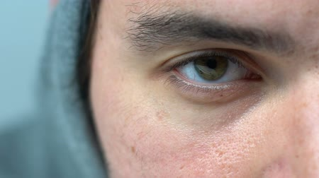 relance : Exhausted green-eyed man in hood blinking looking into camera, macro closeup Vídeos