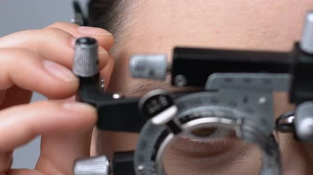 оптический : Lady putting on ophthalmic testing device for eye examination and lens selection