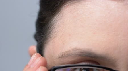 neuritis : Lady putting on glasses to see clearly, problems with vision, nearsightedness