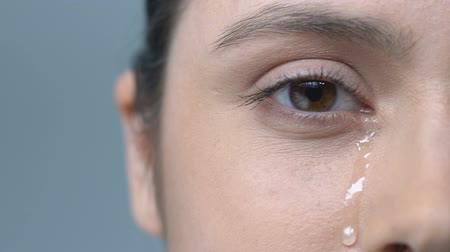 macula : Upset woman crying, drop of tear running down her cheek, eye discharge, problems Stock Footage