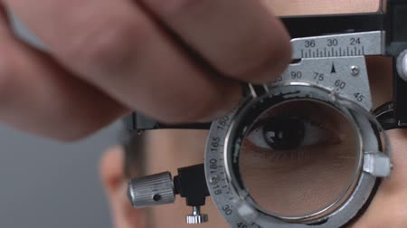 оптический : Professional optometrist putting on lens into phoropter to check patient vision