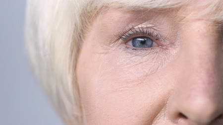 capillari : Old woman with red eyes looking into camera, allergy to cosmetics, lacrimation Filmati Stock