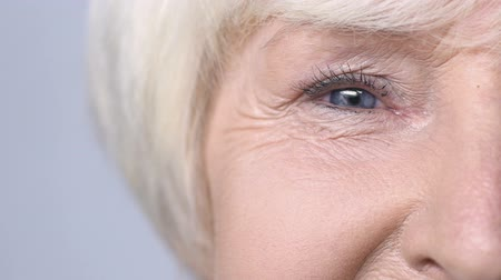 olgun : Mature woman smiling into camera, crows feet wrinkles, anti-aging injections