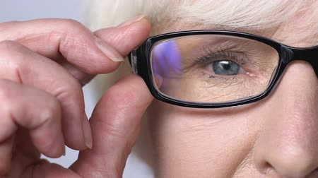 neuritis : Sad old woman with red and tired eyes taking off glasses, eyestrain, presbyopia Stock Footage