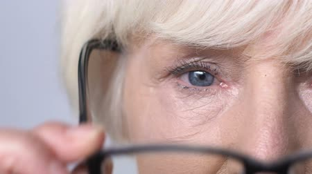 neuritis : Senior woman taking off bad quality glasses and closing eyes, vision problems