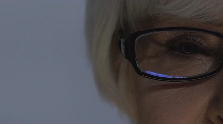 olgun : Senior woman looking into led light, reflection in glasses, vision checkup Stok Video