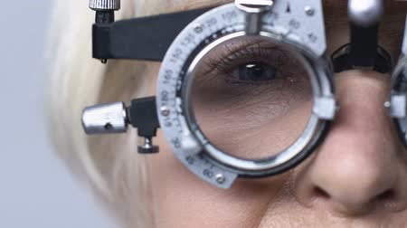 оптический : Old woman in optical trial frame sitting in eye doctor cabinet, vision checkup