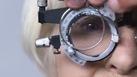 оптический : Eye doctor changing lenses in phoropter, checking mature patient vision, closeup