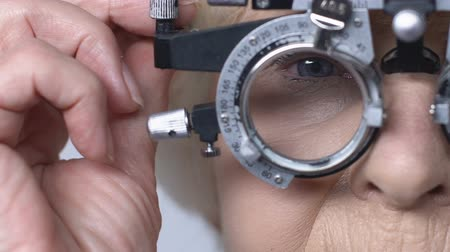 szakértő : Female pensioner checking vision through phoropter, ophthalmology examination Stock mozgókép