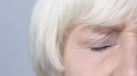 разряд : Retired woman closing her tired eyes, teardrop flowing down cheek, lacrimation
