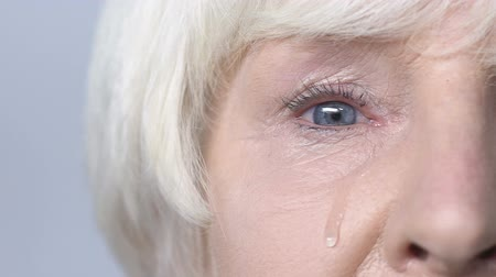 lacrimation : Tear flowing down cheek of sad old woman, eye discharge, lacrimation slow-mo