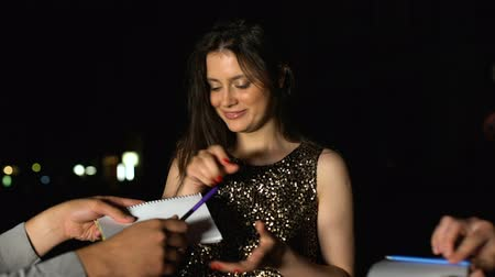 un : Famous woman signing autographs in fans notebooks at evening party, stars life