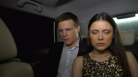 аргумент : Unhappy couple sitting in car backseat after party, relationship crisis bad date