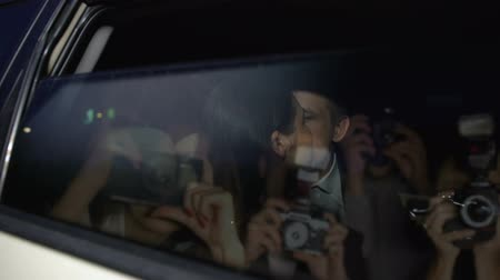 fame : Celebrity couple in car hiding with hand from magazine photographers cameras