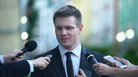 žádat : Successful businessman giving interview on journalist press conference, news