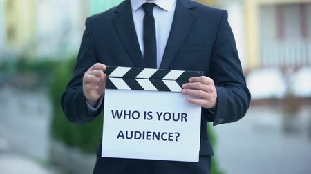 dyrektor : Who is your audience question on clapperboard in hands of male celebrity, pr Wideo