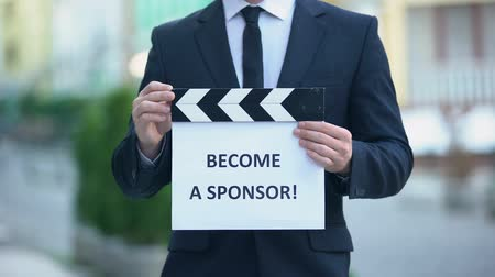 frase : Become a sponsor phrase on clapperboard in hands of producer, independent movie
