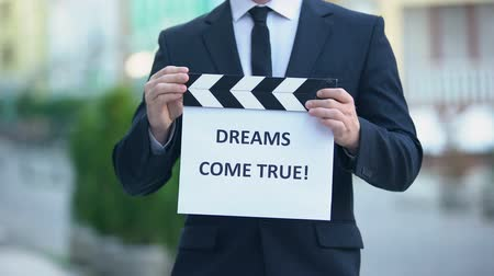 conta : Dreams come true phrase on clapperboard in hands of producer, cinematography