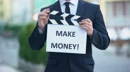 sinematografi : Make money phrase on clapperboard in hands of successful businessman, workshop
