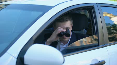 скрывать : Man in suit spying from car using binoculars, private detective investigation