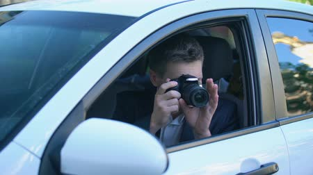 скрывать : Private detective spying from car, taking photos on camera, investigation