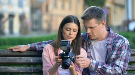 調整する : Male helping girlfriend to make photo with new professional camera, hobby 動画素材