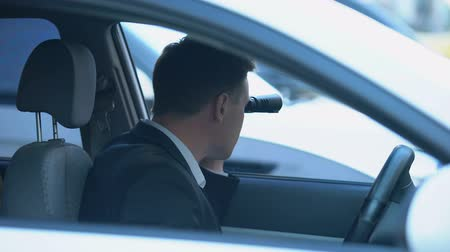 скрывать : Secret spy in car looking through binoculars, confidential information search