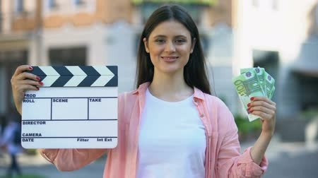 yönetim kurulu : Woman showing clapperboard and bunch of euros at camera, film production worker Stok Video