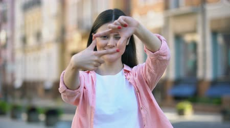 happiness symbol : Smiling woman on street making camera frame gesture with hands, photo focusing Stock Footage