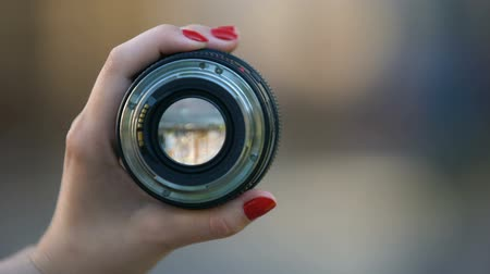 sinematografi : Close-up of womans hand showing camera objective against blurred background