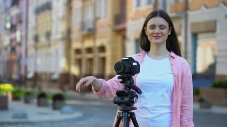 professional photography : Female operator standing near camera with tripod on city street, production