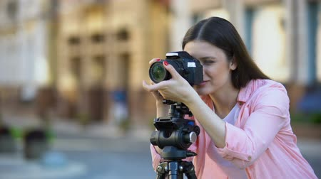 ajustando : Smiling female photographer focusing camera objective on street, photo shooting