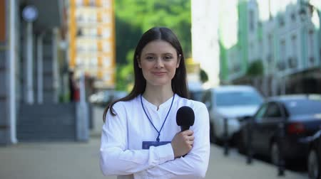 odznaka : Female journalist with microphone and press pass looking at camera on street
