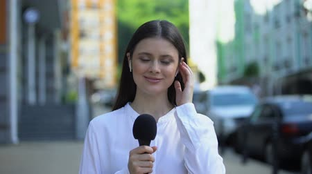 speaker : Female reporter with microphone in headphones talking at camera, live daily news