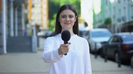 speaker : Female reporter proposing microphone, taking interview on street, daily news